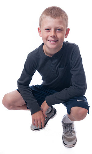 Young man squatting and smiling with cavity free teeth thanks to dental sealants from Great Grins for KIDS in Portland, OR