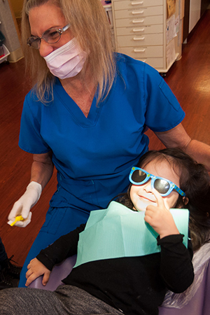 A dental assistant laughing with a young client wearing sunglasses while she relaxes