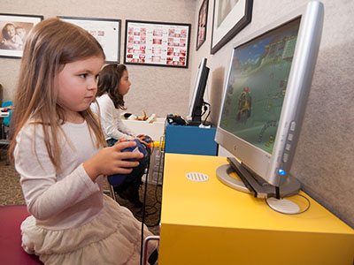 A young child patient of Great Grins for KIDS - Portland plays a computer game before her appointment