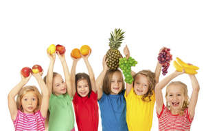 Kids holding up fruit and other healthy foods for Great Grins for KIDS - Portland.